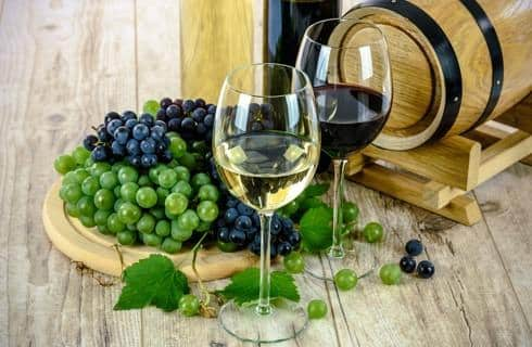 Green and purple grapes next to wine glasses with white and red wine