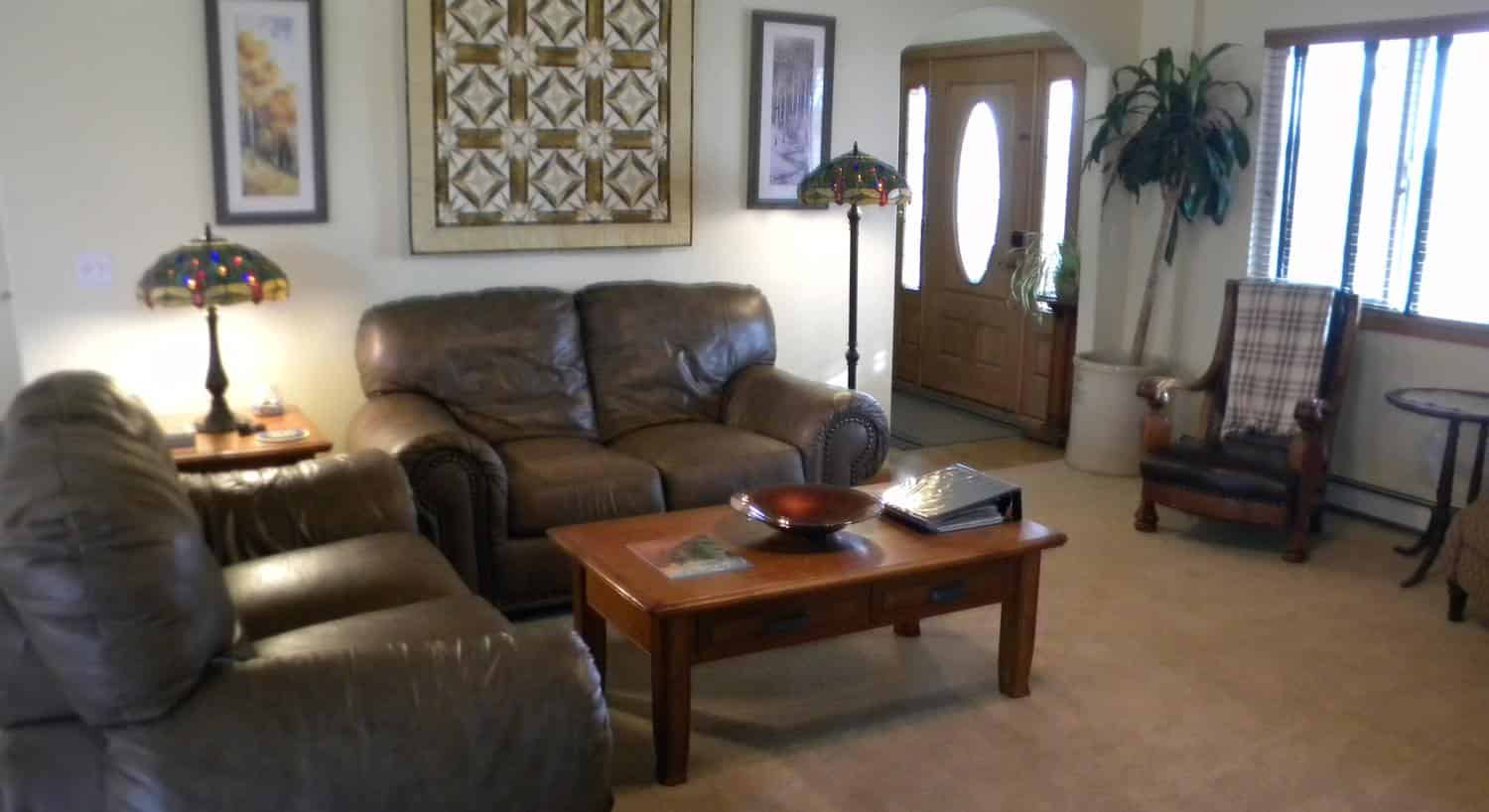 Livingroom with large brown leather loveseats and wooden coffee table