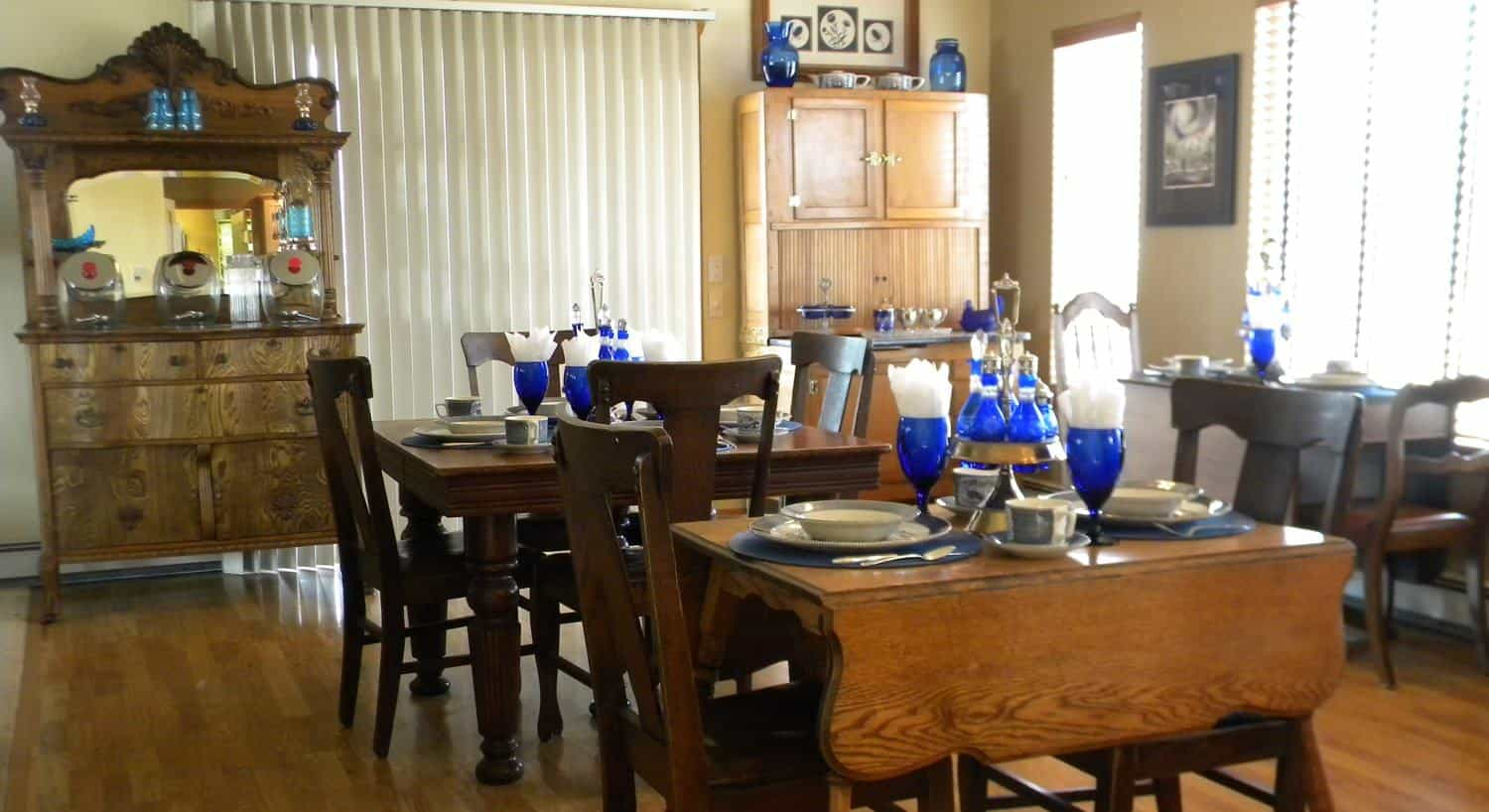 Dining room with brown wooden tables and chairs with blue and white place settings and blue glasses