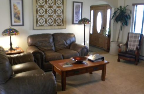 Livingroom with brown leather love seats and wooden coffee table