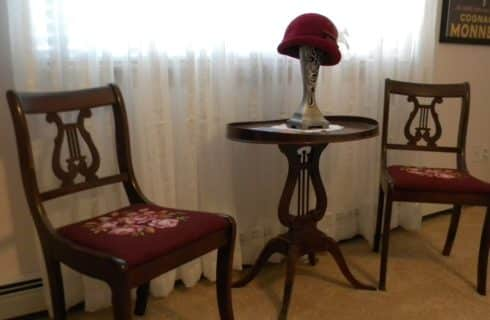 Antique table and chairs next to sheer white curtains