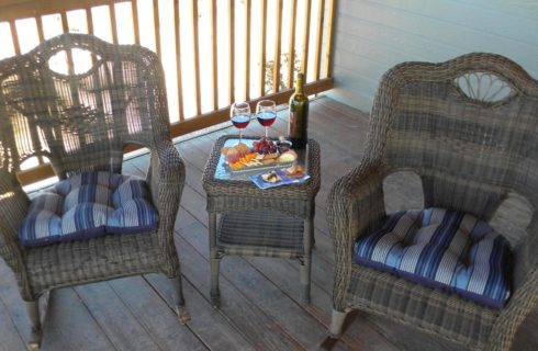 Wooden porch with wicker patio chairs and table