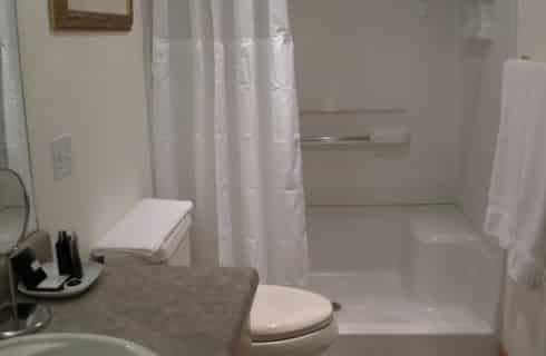 Bathroom with white walls, white curtains, and white toilet