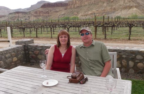 Trey and Annette sitting at wooden table in front of vineyard