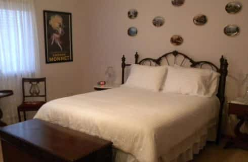 Bed with rod-iron headboard and white bedding