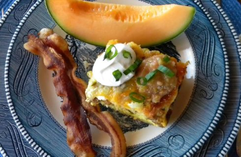 Plate with baked egg dish, bacon, and canteloupe
