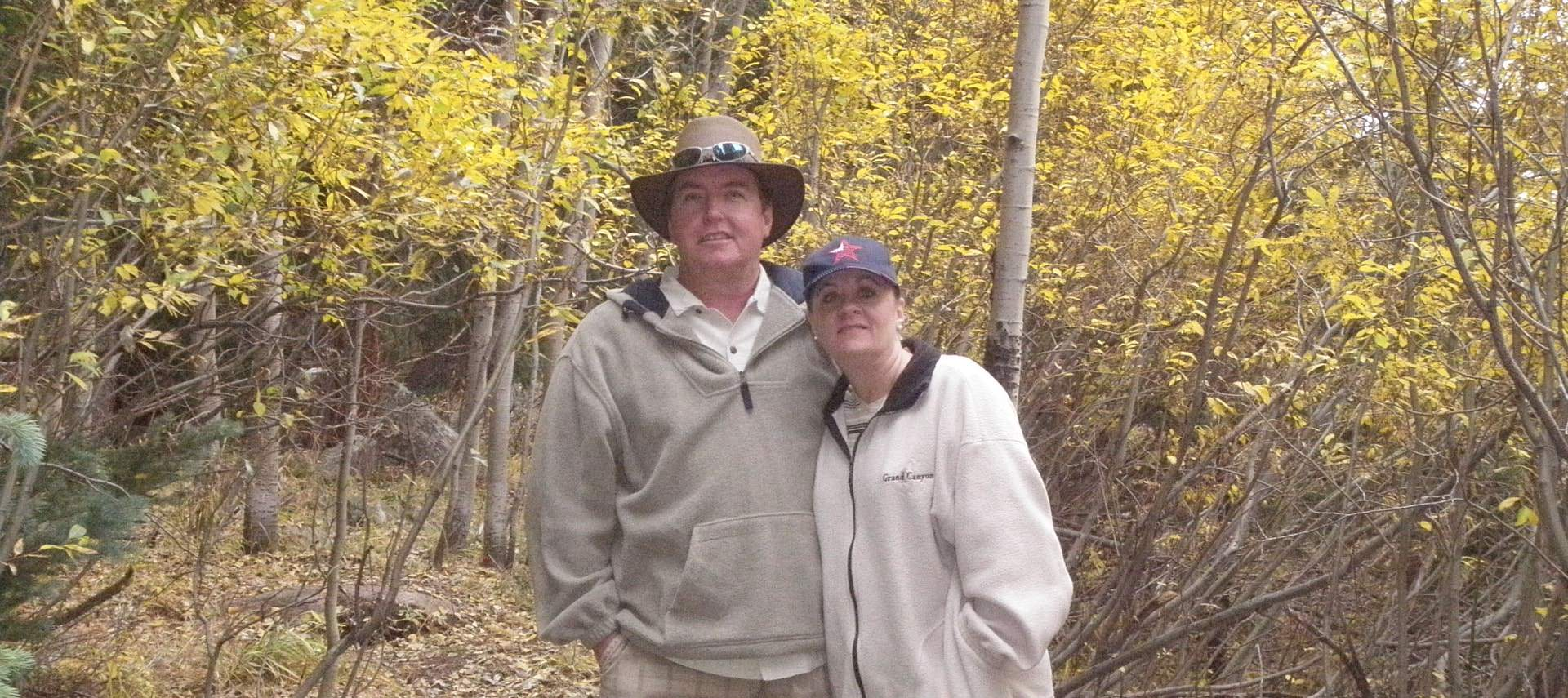 Two people hiking in the woods among trees with yellow leaves
