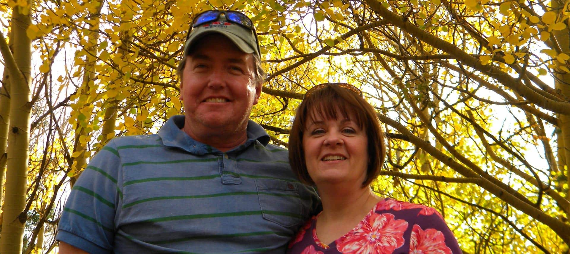 Trey and Annette standing near trees with green leaves