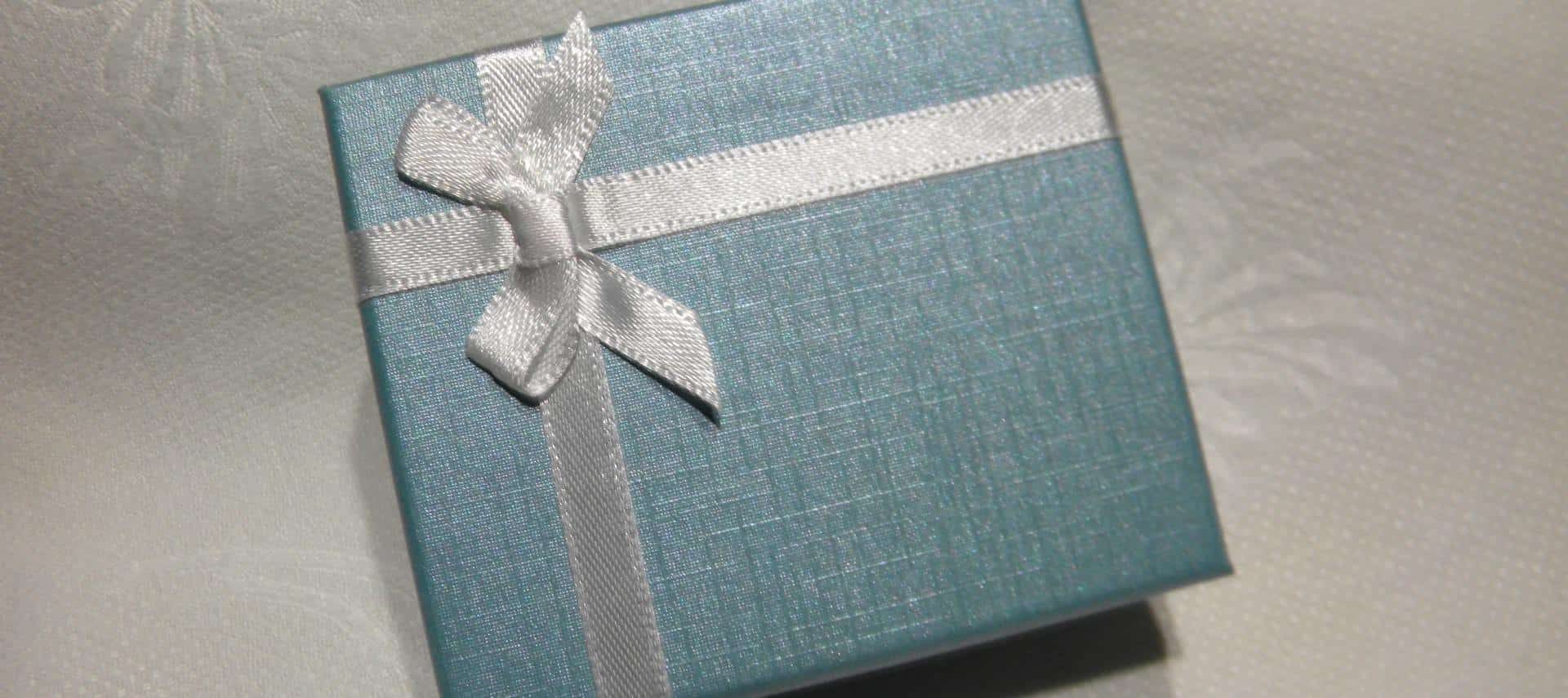 Gift box wrapped in blue paper with white bow