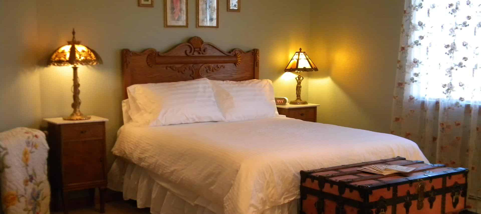 Bed with brown wooden headboard and white bedding