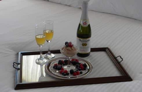 Tray with chocolate covered strawberries and Champagne on a bed with white bedding