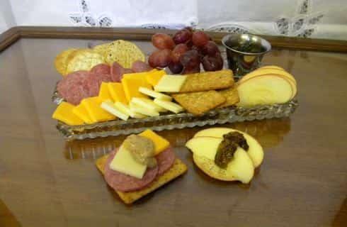 Glass tray with various meats, cheeses, and fruit